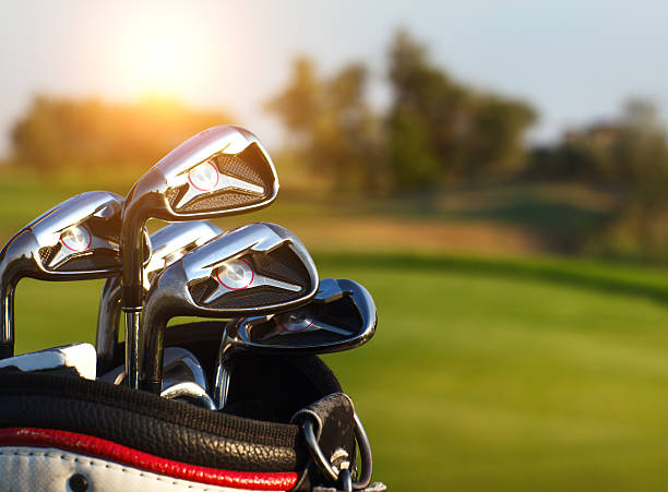 golf clubs drivers over green field background - golf clubs stock photos and pictures
