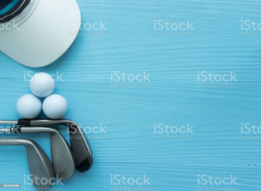 Golf clubs, golf balls, cap, on blue wooden table stock photo
