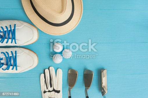 istock Golf concept : panama hat, glove, golf balls, golf clubs, golf shoes on wooden table. Flat lay with copy space. 672741460