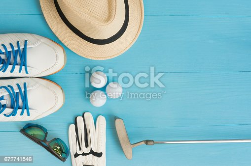 istock Golf concept : panama hat, glove, golf balls, golf clubs, golf shoes, sunglasses on wooden table. Flat lay with copy space. 672741546