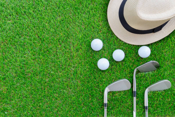 Conceito de golfe: Chapéu Panamá, bolas de golfe, campo de golfe ferro clubes na cama plana em vidro verde, com espaço de cópia. - foto de acervo
