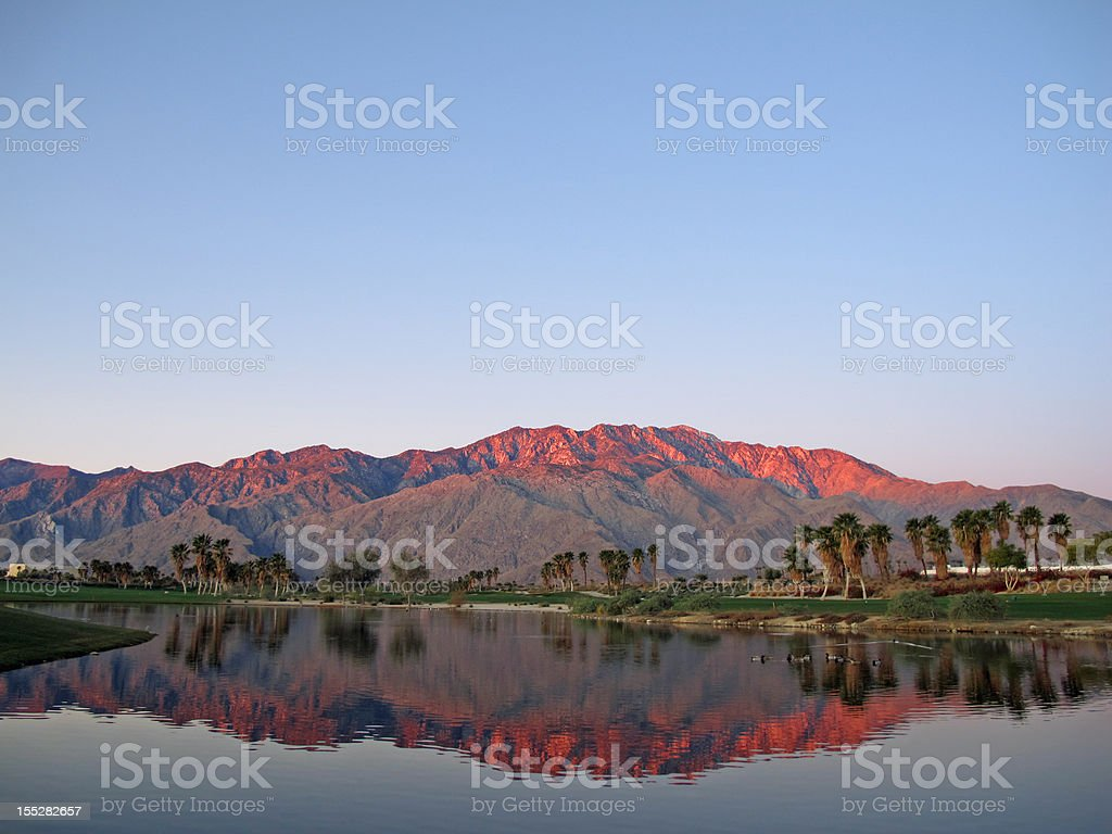 Golf course at dawn with sunrise kissed mountains stock photo