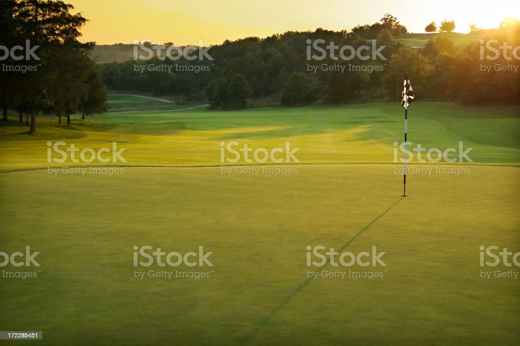 A golf course at dusk with trees in the distance stock photo