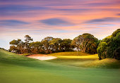 Sun setting on a golf course with the green and pin in view surrounded by trees.