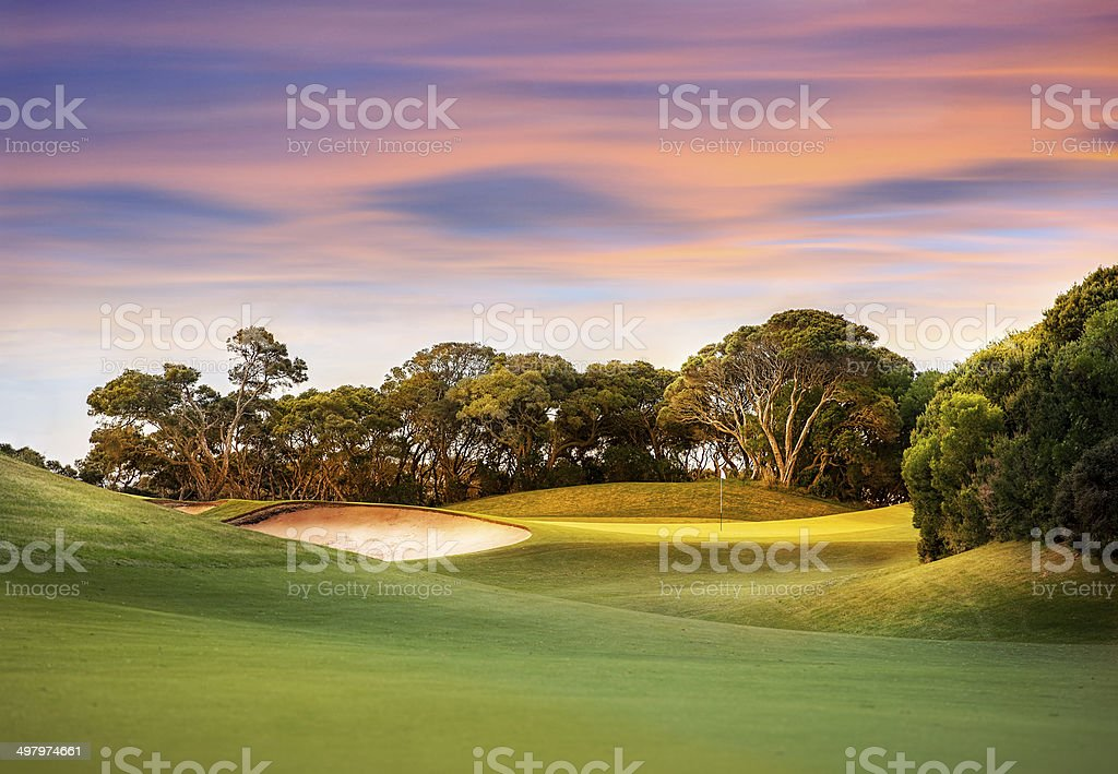 Golf Course at Sunset with light on the green stock photo