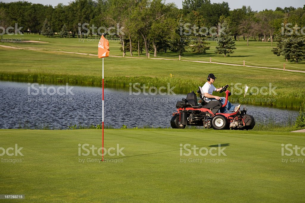 A golf course maintenance worker who is cutting the grass  stock photo