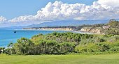 Golf Course Overlooking Ocean and Pier in Santa Barbra California. Perfect balance of white clouds, grass, and ocean pier that are laid out in a parallel pattern.