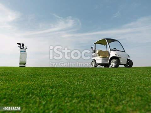 wide angle shot of grass, golf clubs and golf car in a
