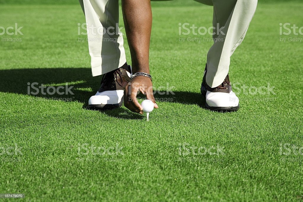 Golf course Tee green grass African American male shoes ball royalty-free stock photo