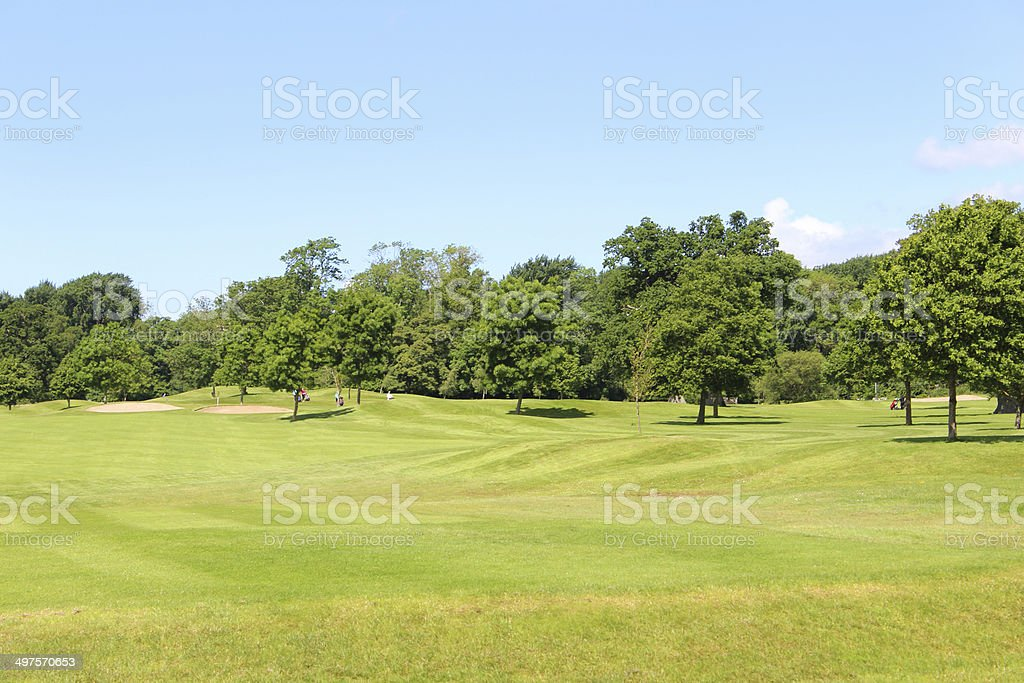 Photo showing a landscaped golf course with neatly cut green grass,...