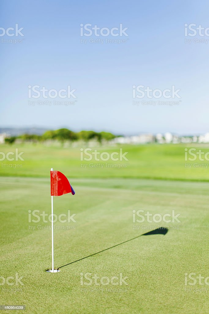 Golf course with red flag on putting green royalty-free stock photo