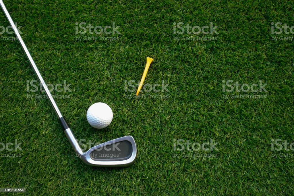 Golf equipment on green grass.Golf balls,tee and golf clubs in the...