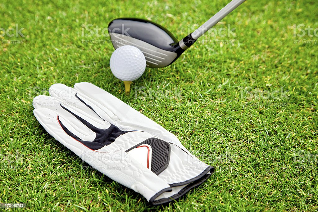 Golf ball on the tees with driver golf stick and glove at the golf...