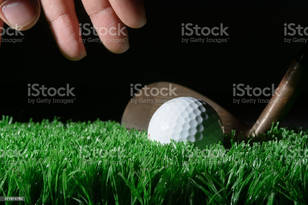 a hand grabs for the golf ball with a wedge sitting behind the golf...