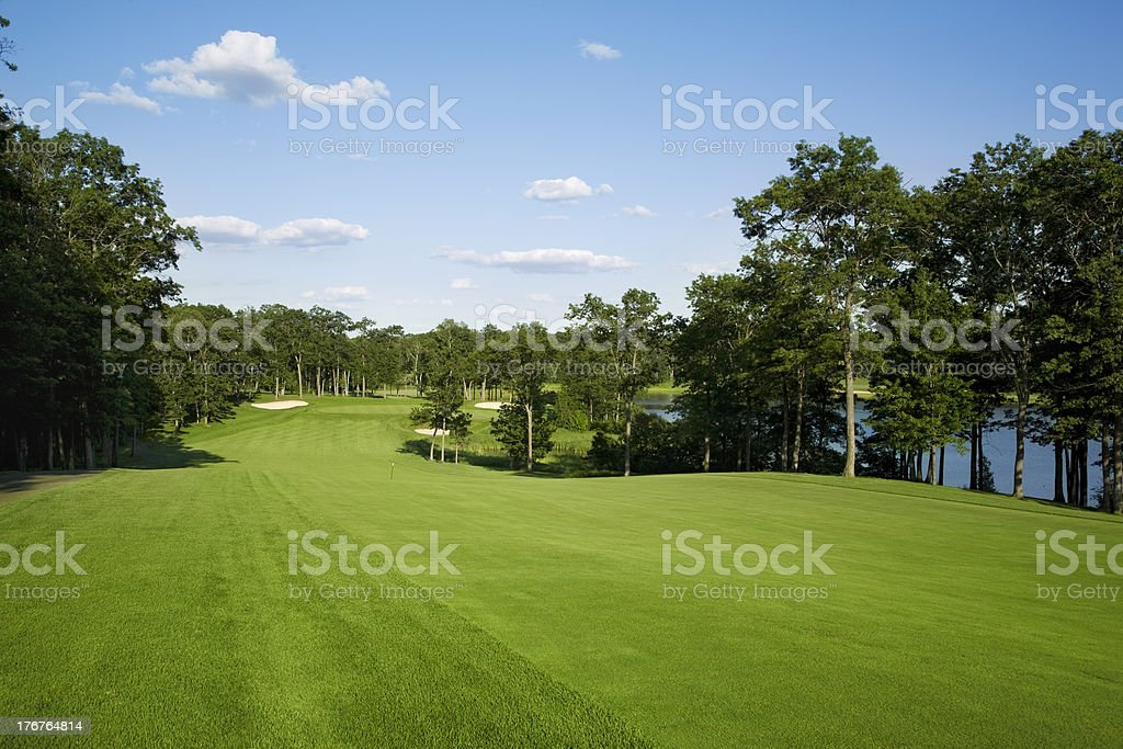 Golf fairway lined with trees near lake - Royalty-free Blue Stock Photo