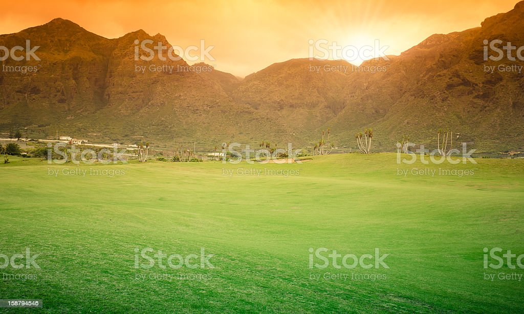 Golf field against mountain during gold sunset royalty-free stock photo