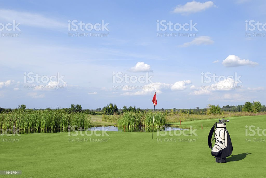 golf field with red flag and bag royalty-free stock photo