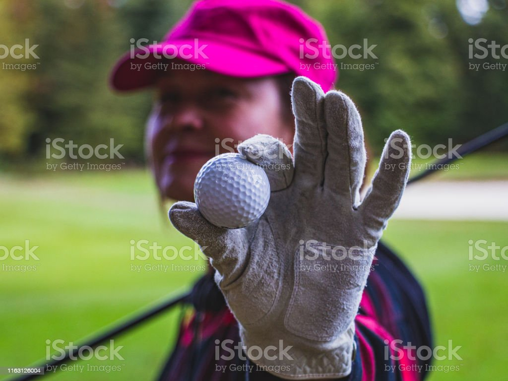 An active middle-aged golfer with a pink cap shows the viewer a golf...