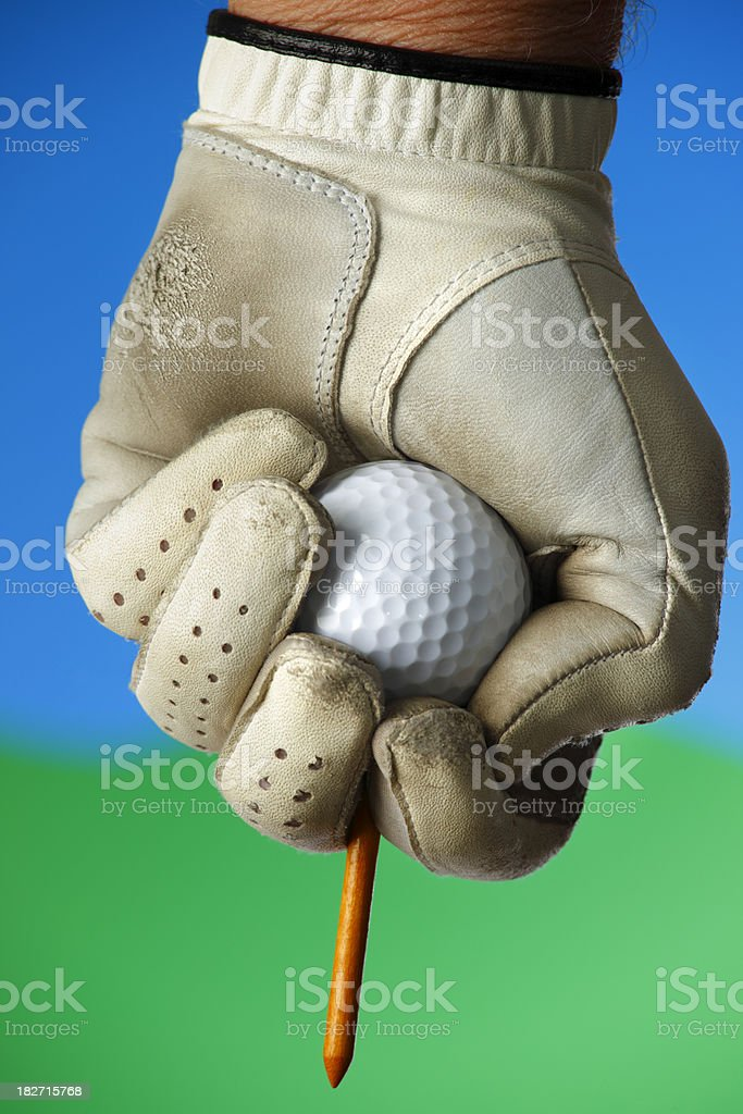 Golfer ready to tee up his golf ball with a worn leather glove.