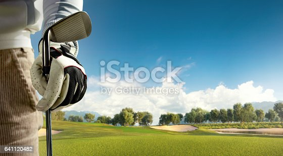 View of the green rolling landscape and bunkers or sand traps with a bag full of golf putters at Golf course. The golf field is made in 3D.