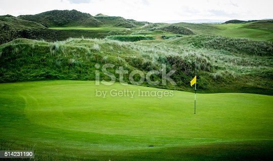 Yellow flag marking the hole on a golf green