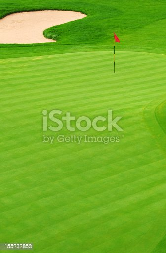 825397576 istock photo Golf green with sand bunker and red flag marking hole 155232853