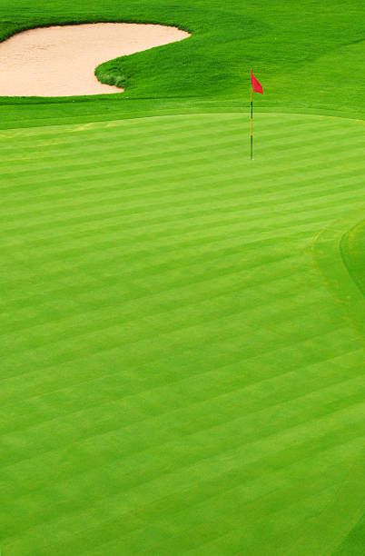 Golf green with sand bunker and red flag marking hole Golf Green green golf course stock pictures, royalty-free photos & images