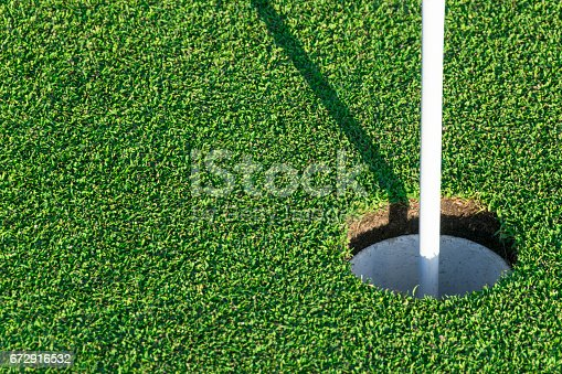 825397576 istock photo Golf hole on green grass of golf course. View of golf hole on green field. 672916532