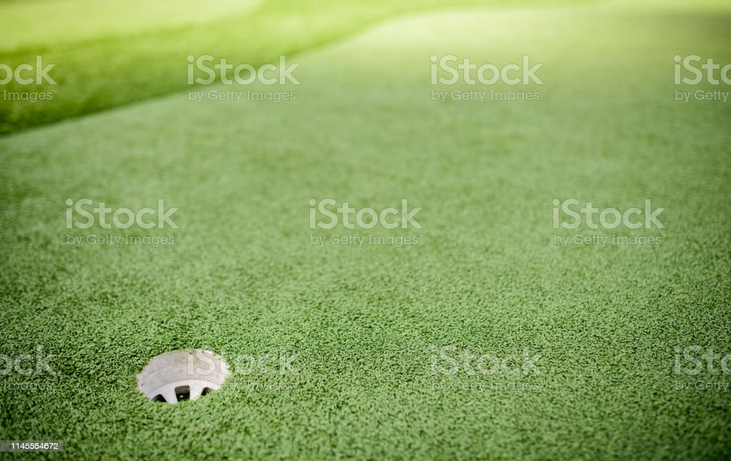 Image of Golf hole on green in golf course.