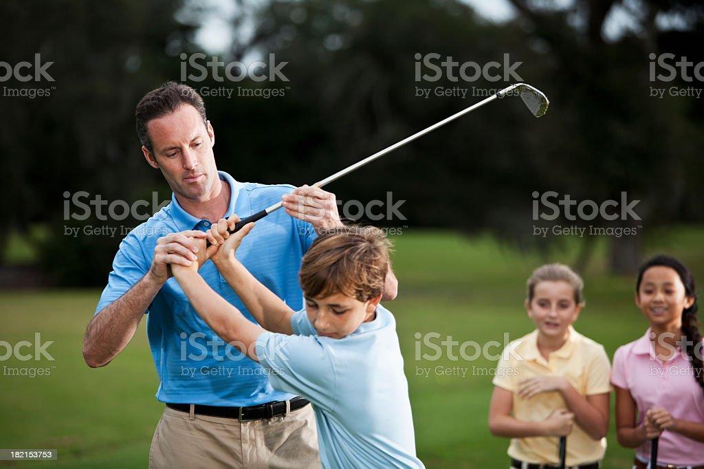 Golf instructor adjusting boy's grip royalty-free stock photo