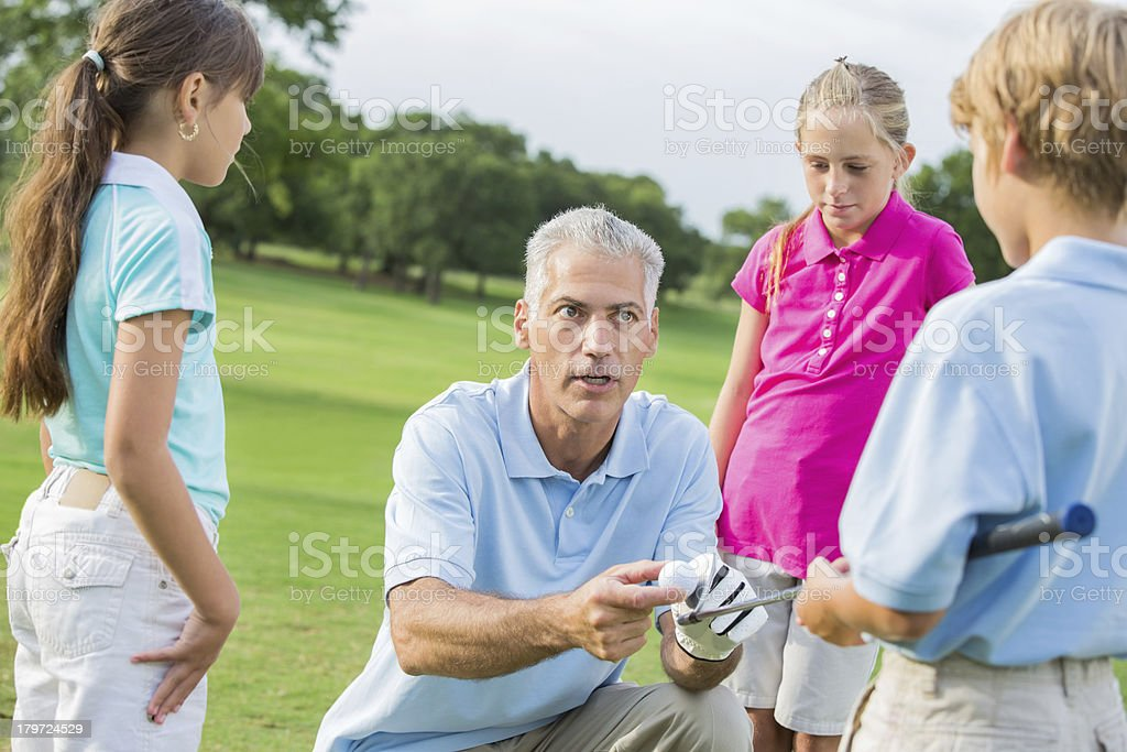 Golf instructor teaching class to young students royalty-free stock photo