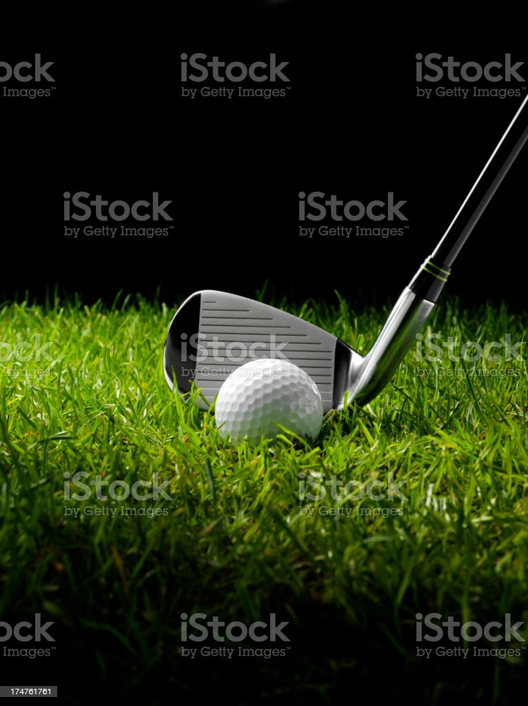 Golf Iron with a Ball and Tee on grass stock photo