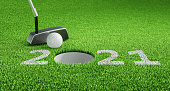 White Numbers 2021 of new Year on green Grass Background with Golf Ball and Putter