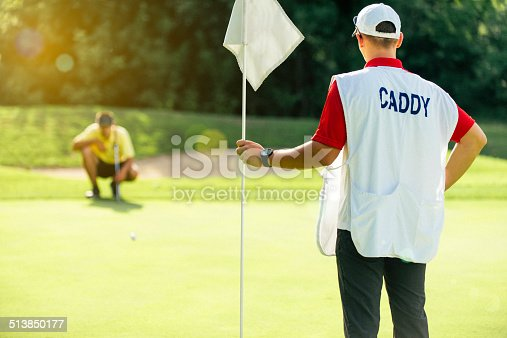 Golf - caddy holding flag, golfer reading green