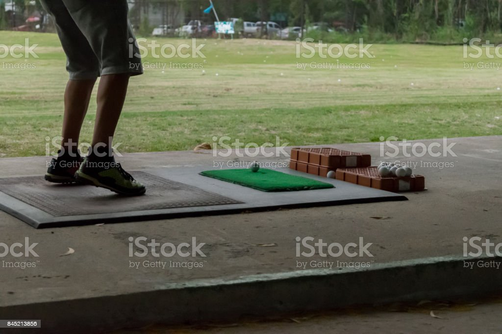 Golf player and Golf ball white color in golf club on green for sport training stock photo