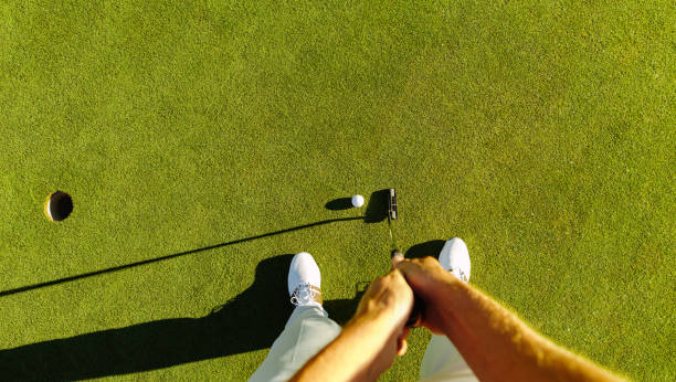 Golf player at the putting green hitting ball into a hole stock photo