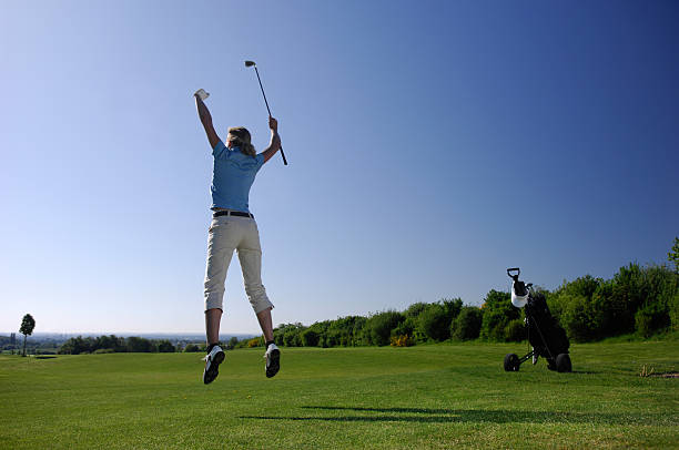 Golf player on course jumping and celebrating stock photo