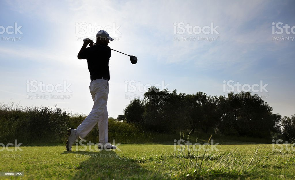 Golf Player. Perfect shot on the Course. Sunset. Contre jour. stock photo