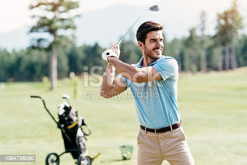 Golf player swinging on the course