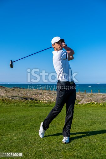 Young man plays golf in a Spaniard course in a sunny day