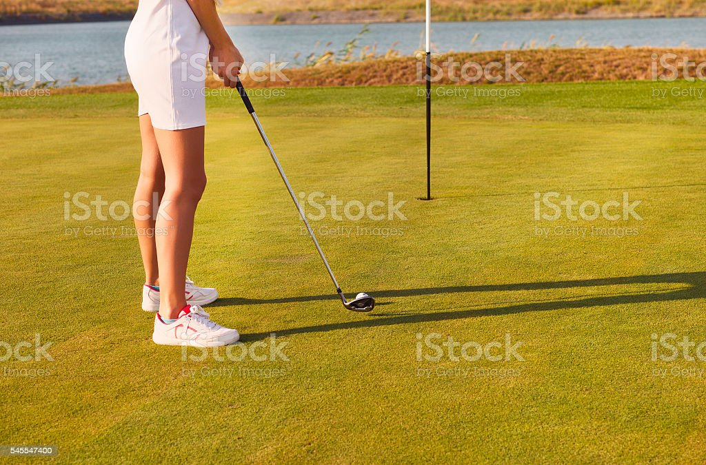 Golf player practicing to hit a ball at the course stock photo