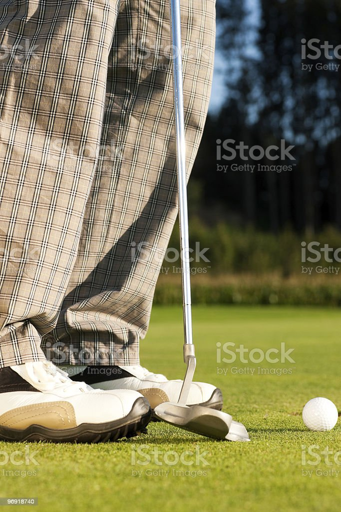 Golf player putting ball in hole royalty-free stock photo