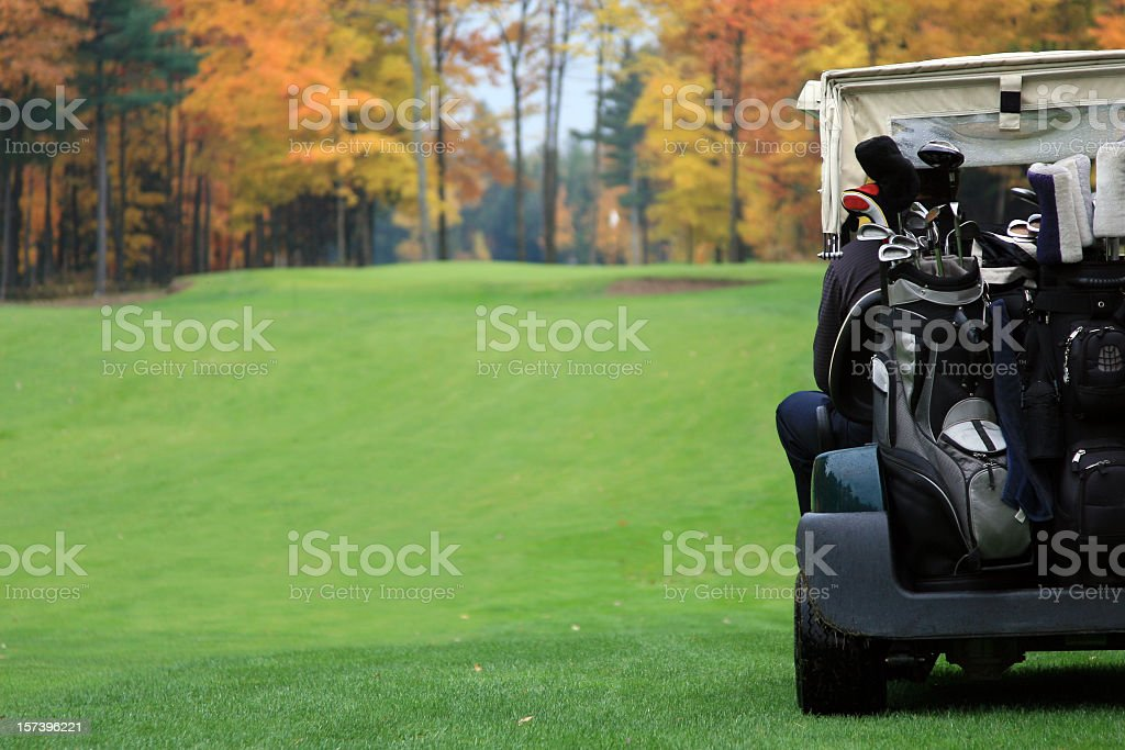 Golf Player Riding in Golf Cart Towards Putting Green stock photo