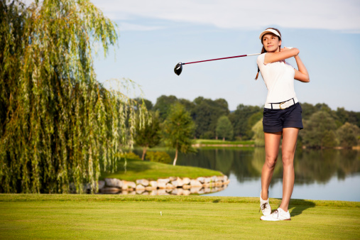 A golf player teeing off on a sunny day