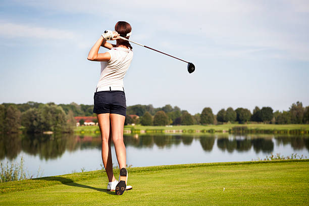 Golf player teeing off stock photo