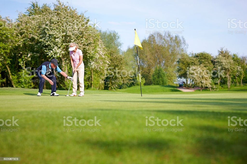Golf pro teaching the proper putting technique stock photo