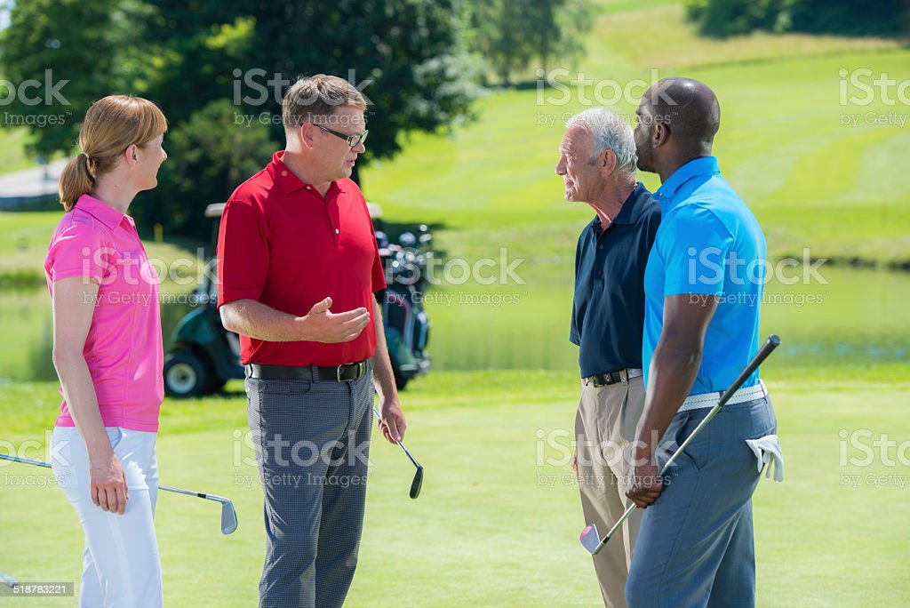 Golf Pro With Group of Adult Golfers stock photo