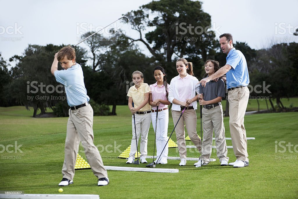 Golf pro with group of children on driving range royalty-free stock photo