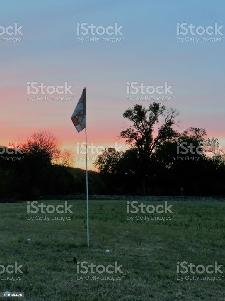 golf putting practice hole at sunset stock photo