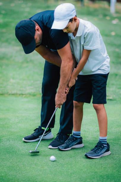 Golf Putting Training. Golfinstructor mit Young Boy Üben auf dem Putting Green – Foto
